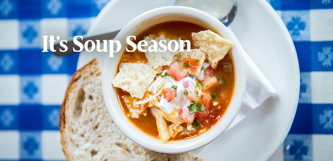 Bowl of Taco Soup with a slice of fresh bead on Merridee's blue gingham tablecloth